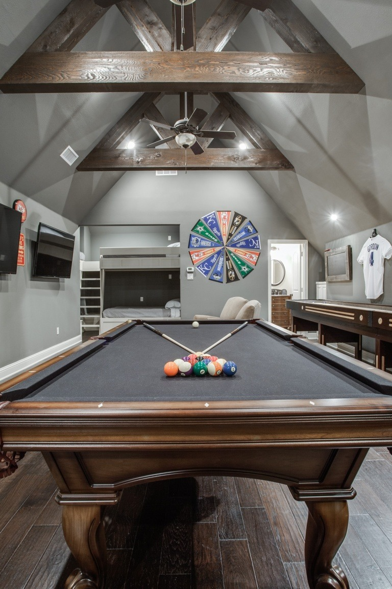 attic room addition with a pool table, tvs, bunkbeds, bathroom, and sports flags on the wall.