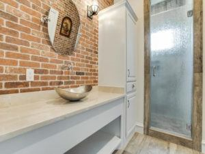Bathroom Remodel - modern bathroom with brick wall and metal bowl sink