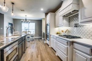 home makeover mistakes - grey and white remodeled kitchen with island and wood floors