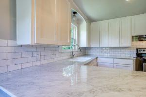 kitchen features worth the investment - white updated kitchen with subway tile backsplash