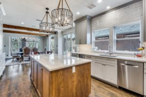 home makeover mistakes - remodeled kitchen with wood island and hanging light fixtures