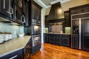 kitchen cabinets - kitchen with dark cabinetry and wood floors