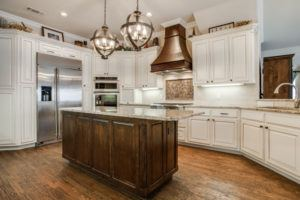 kitchen design trends - kitchen with wood centerpiece range hood over stove