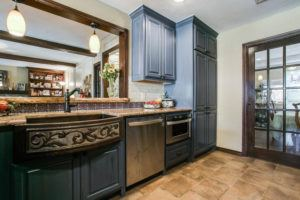 kitchen design trends - kitchen with dark blue cabinets and statement sink