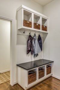 back to school organization tips - hooks and seating bench in entryway of home