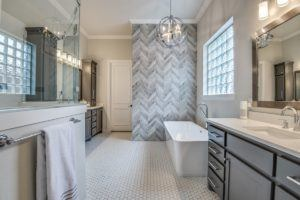 bathroom remodel - updated grey and white bathroom with accent wall and white bathtub